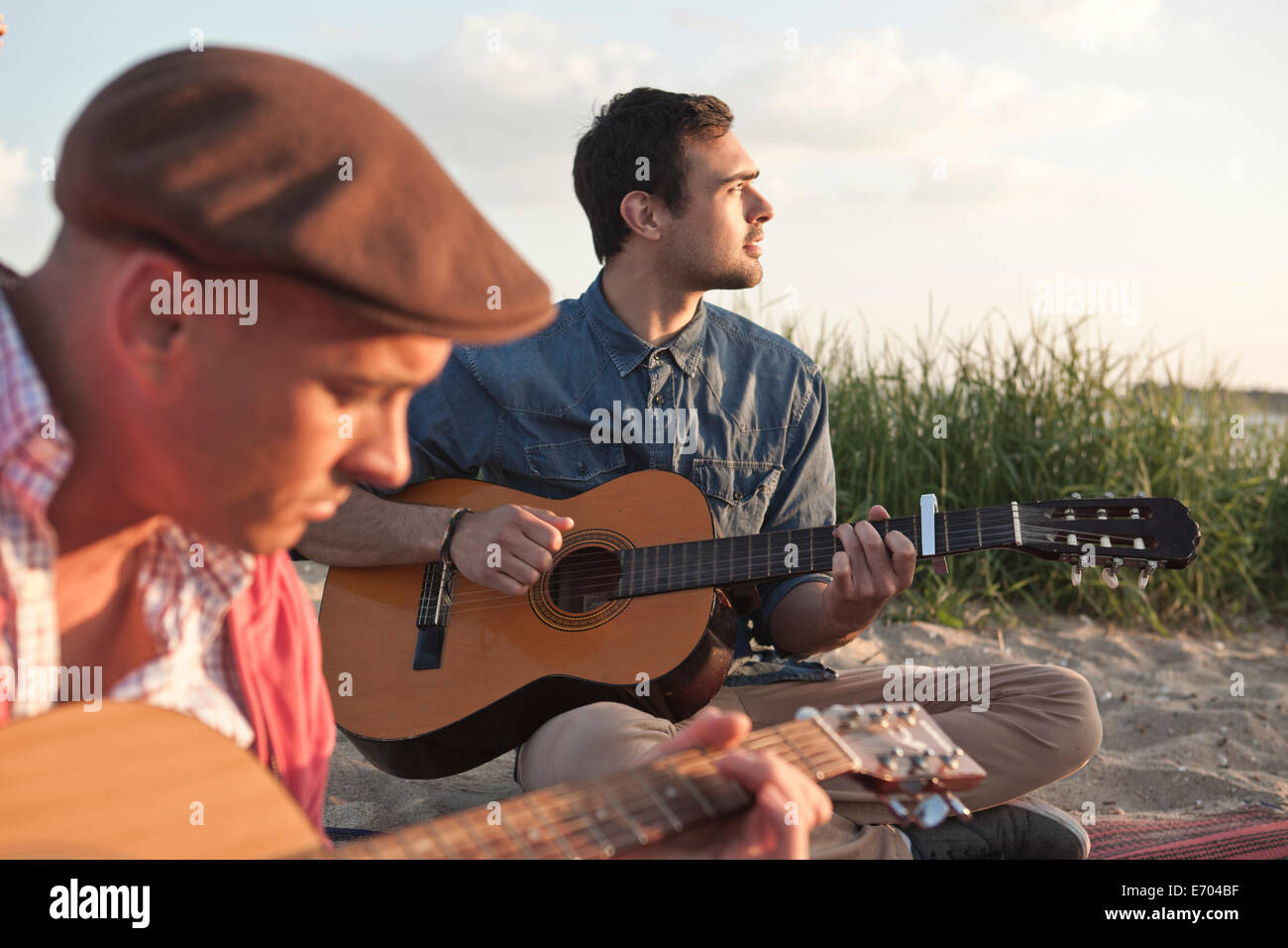 Two adult male friends playing acoustic guitars on Bournemouth beach, Dorset, UK - Stock Image