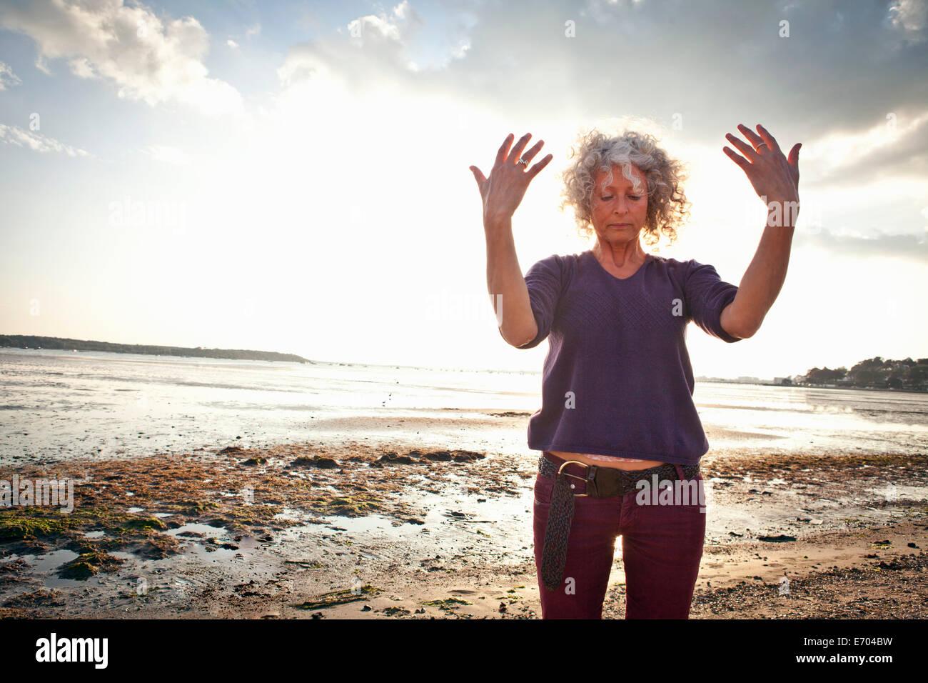 Mature woman exercising on beach Stock Photo