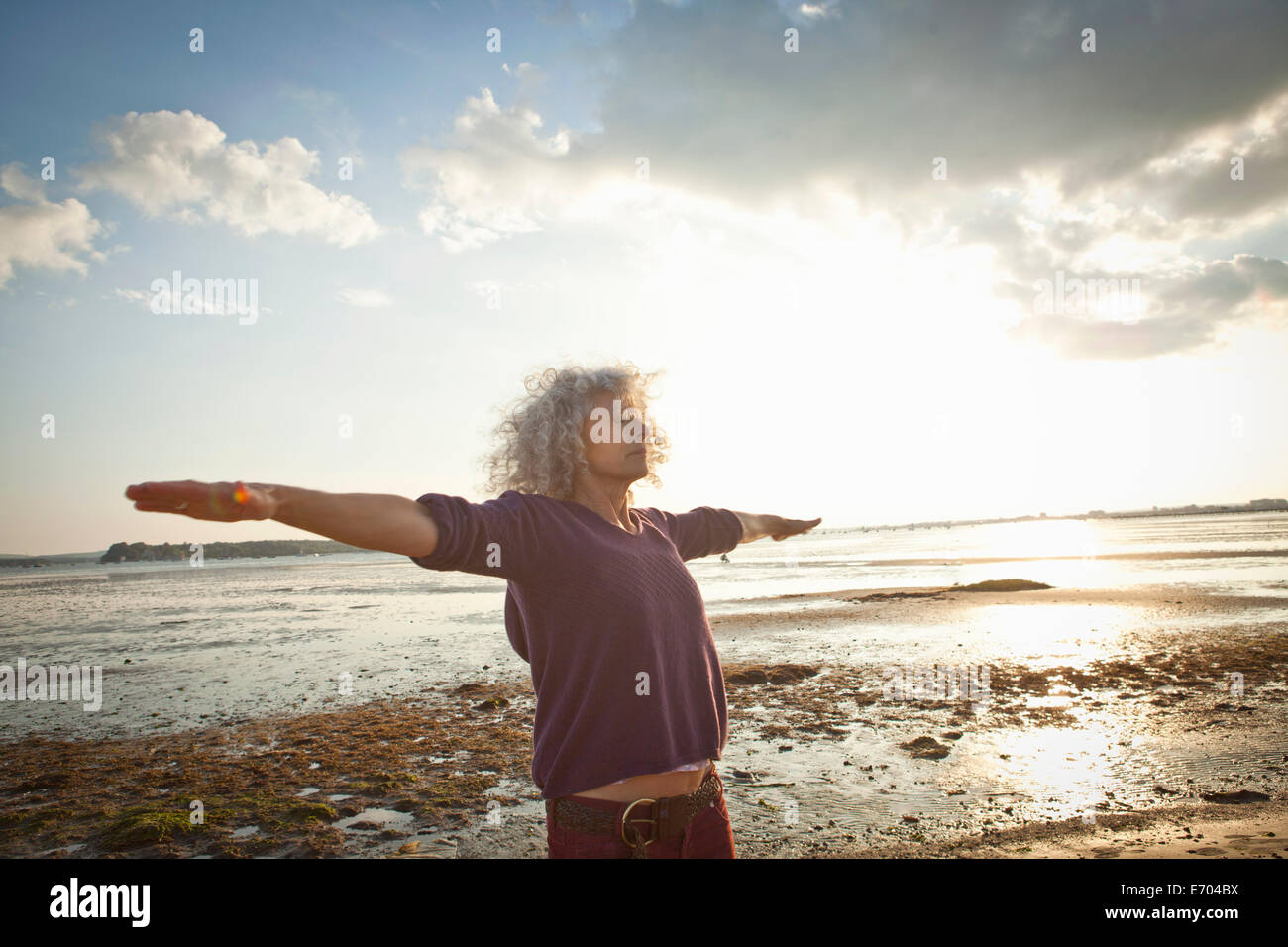 Mature woman exercising on beach - Stock Image