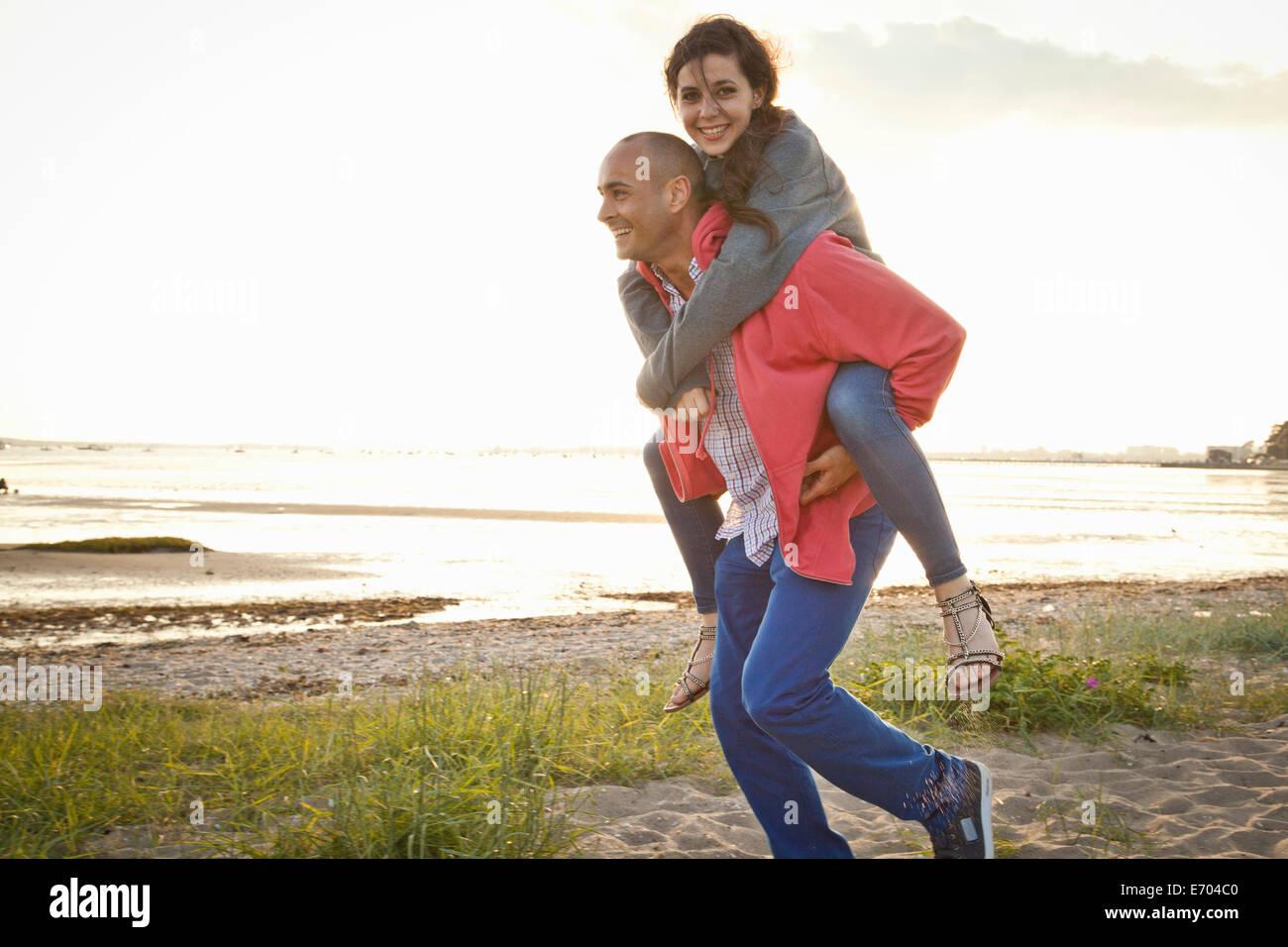 Man giving piggyback ride to woman on beach - Stock Image