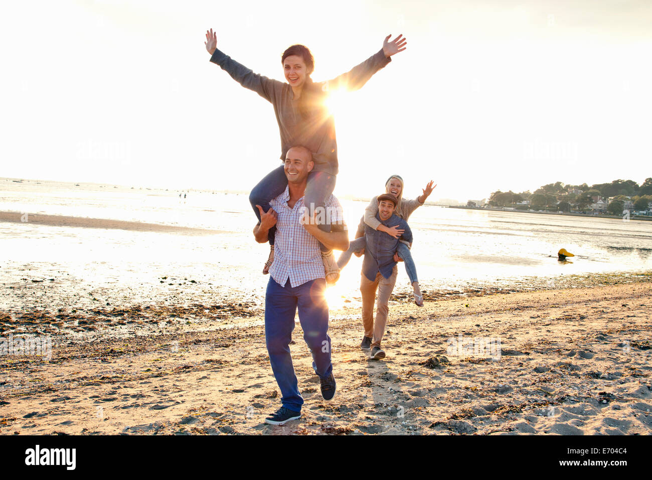 Men giving piggyback ride to women on beach Stock Photo