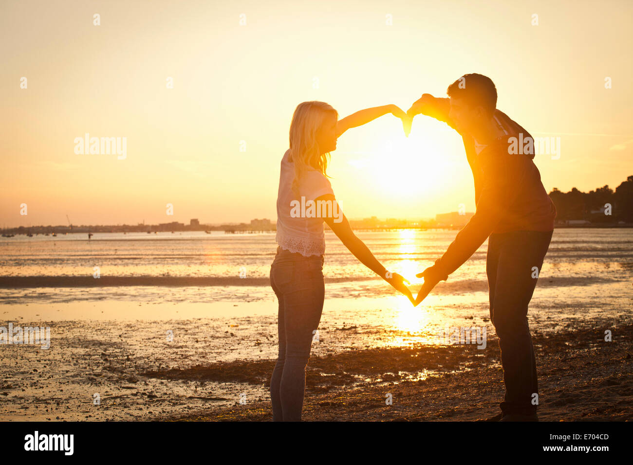 Couple forming heart shape with arms on beach at sunset - Stock Image