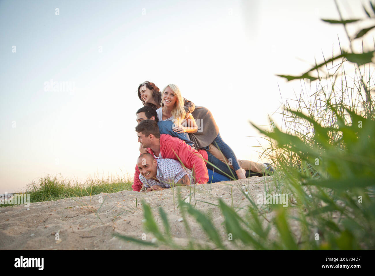 Group of friends making human pile on beach Stock Photo