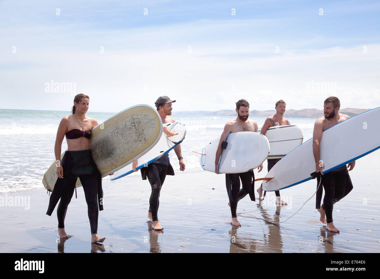 Group of male and female surfer friends walking away from sea with surf boards - Stock Image