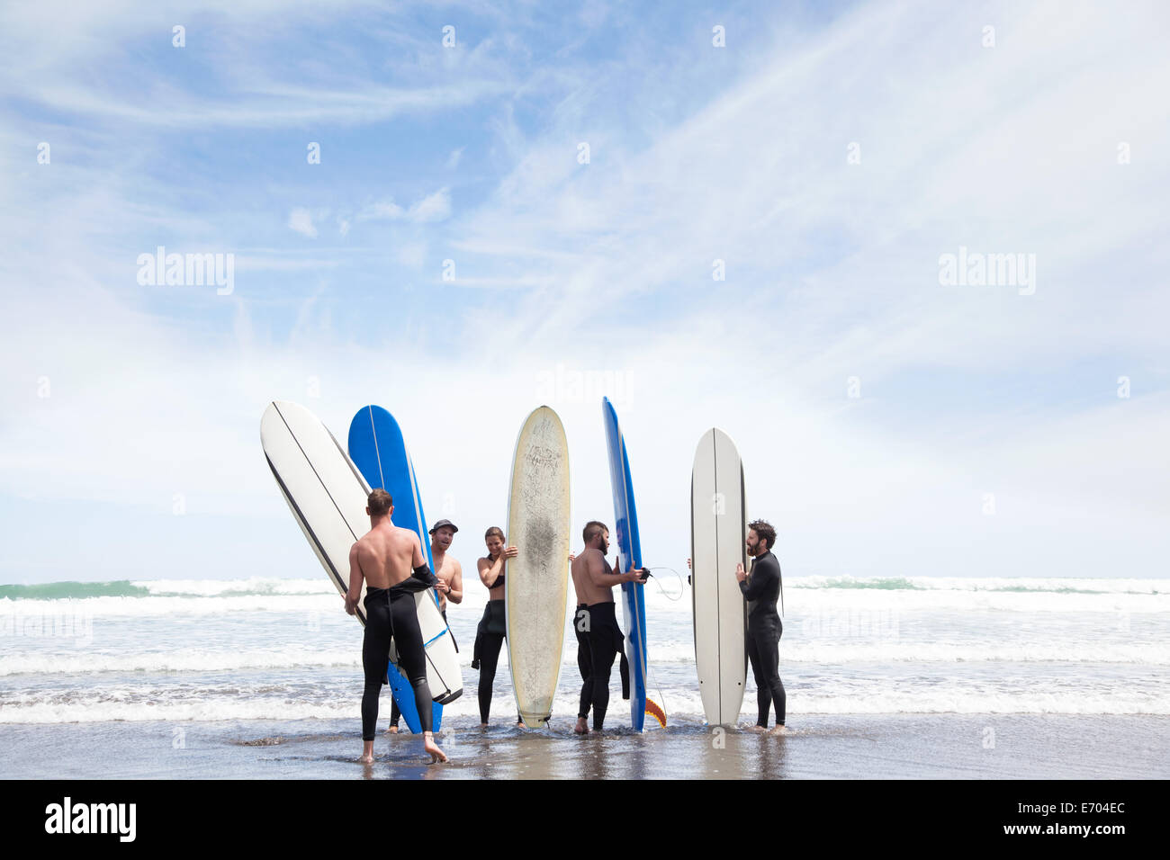 Group of male and female surfer friends standing on beach with surf boards - Stock Image