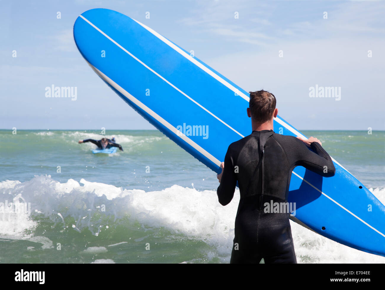 Rear view of male surfer with surfboard watching friend surfing - Stock Image