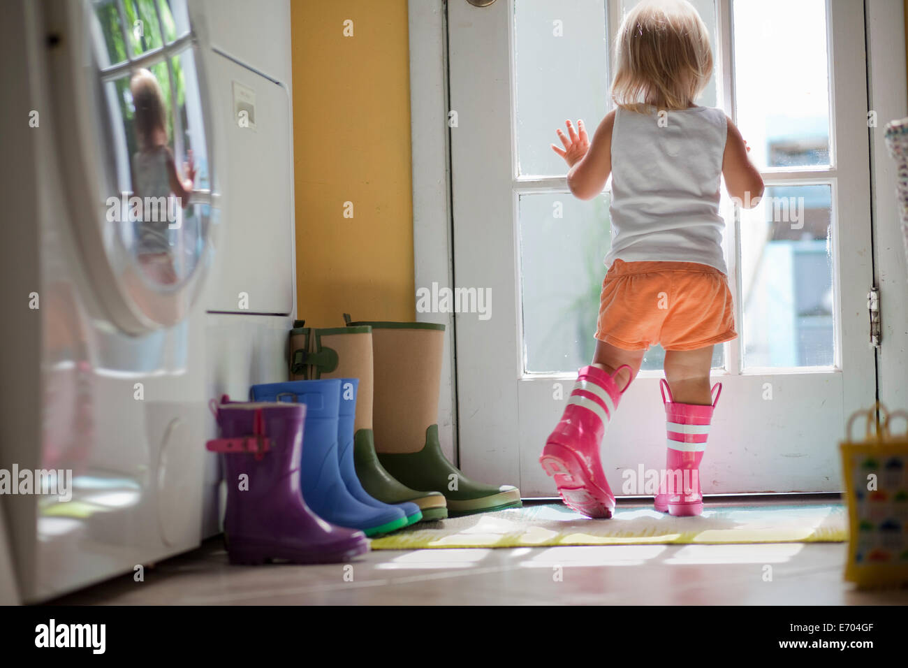 Female toddler wearing rubber boots looking out of back door window - Stock Image