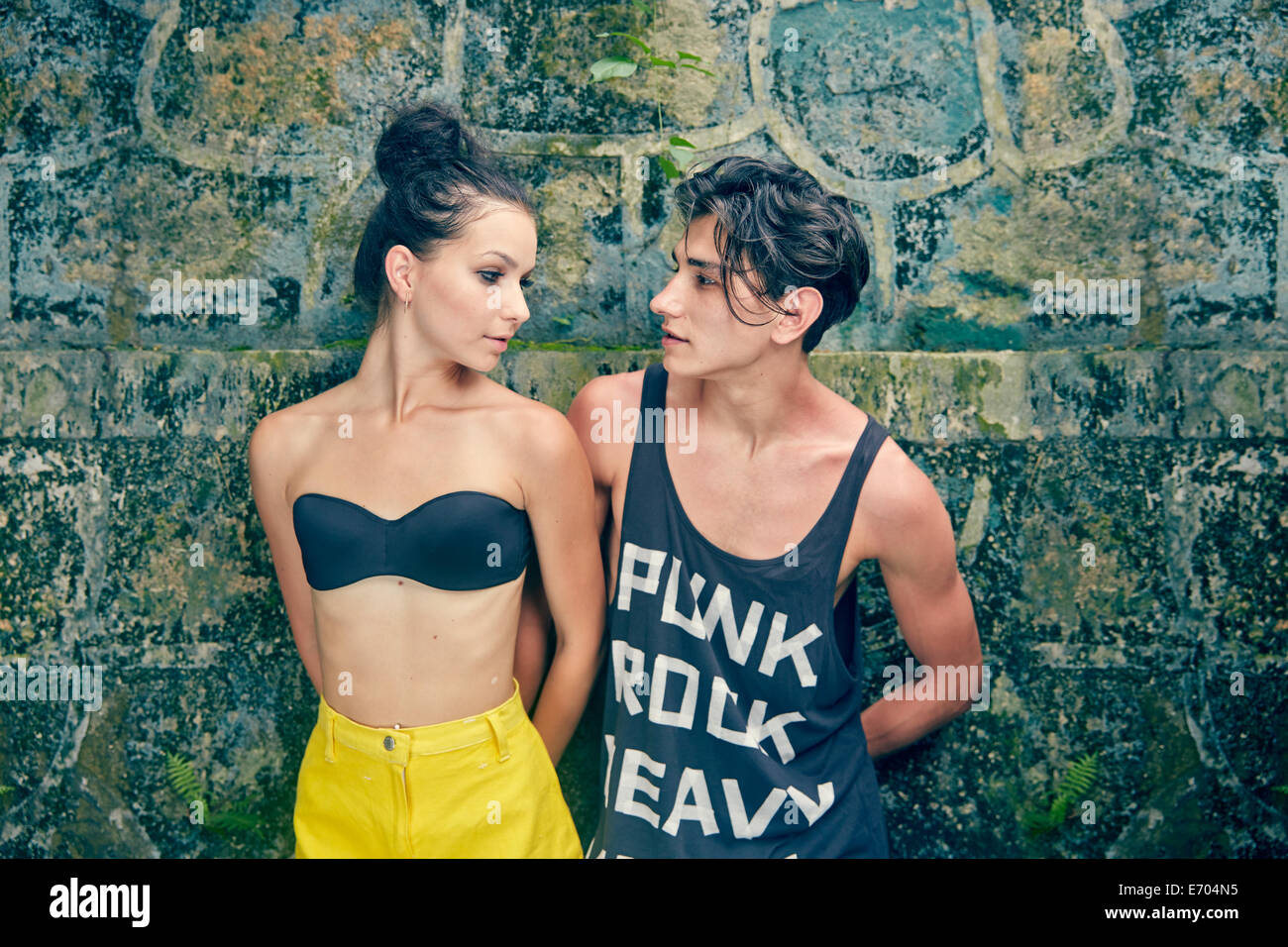 Young couple standing against wall, looking at each other - Stock Image