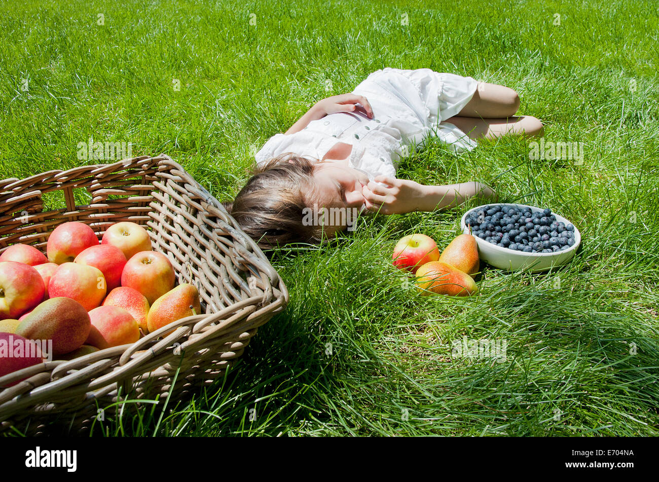 Girl asleep on grass with basket of apples and pears - Stock Image