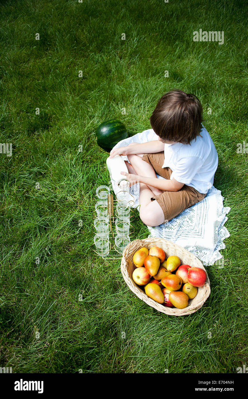 Overhead view of boy cross legged on grass pouring milk into glasses - Stock Image