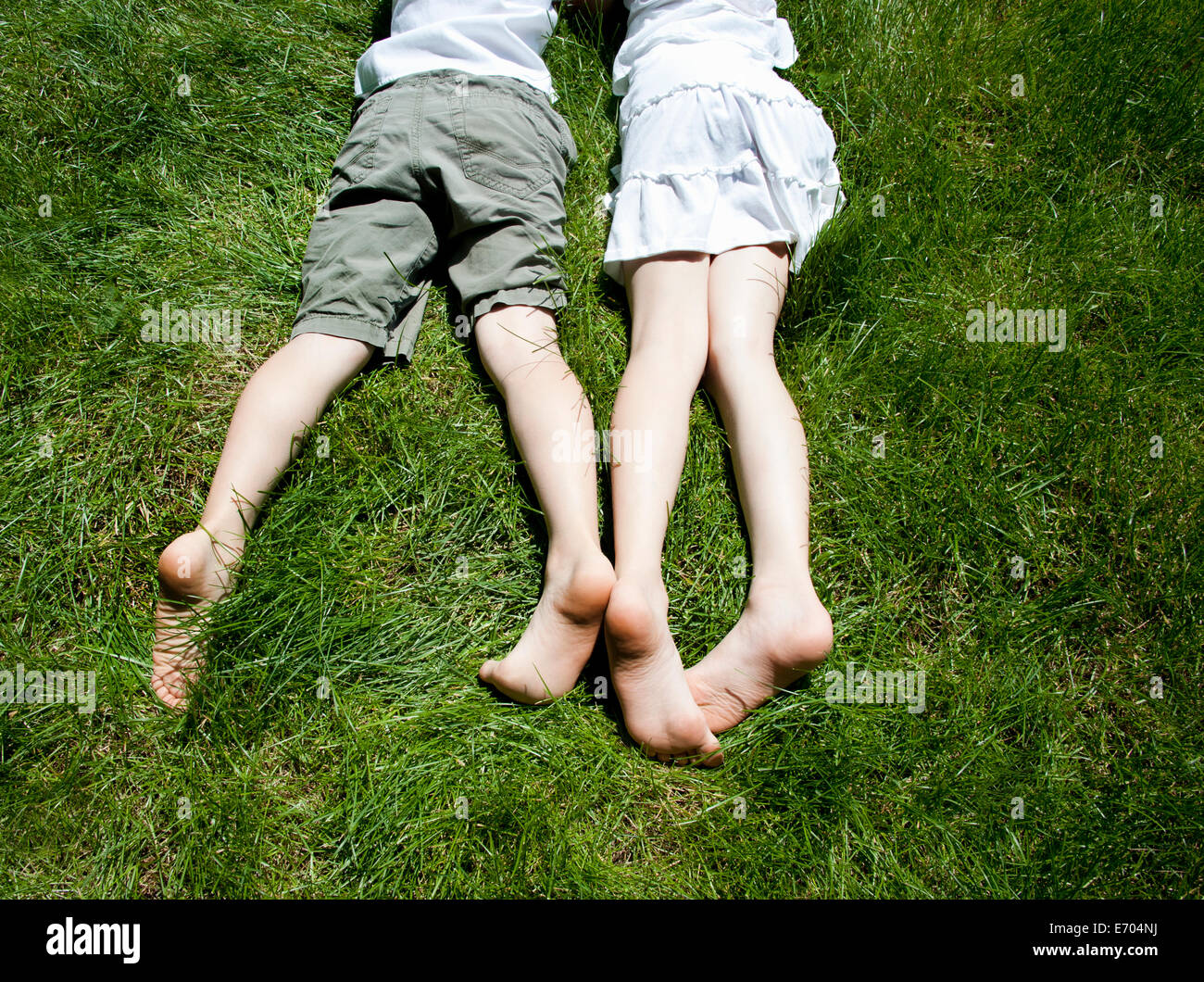 Overhead view of brother and sisters legs as they lay on grass - Stock Image