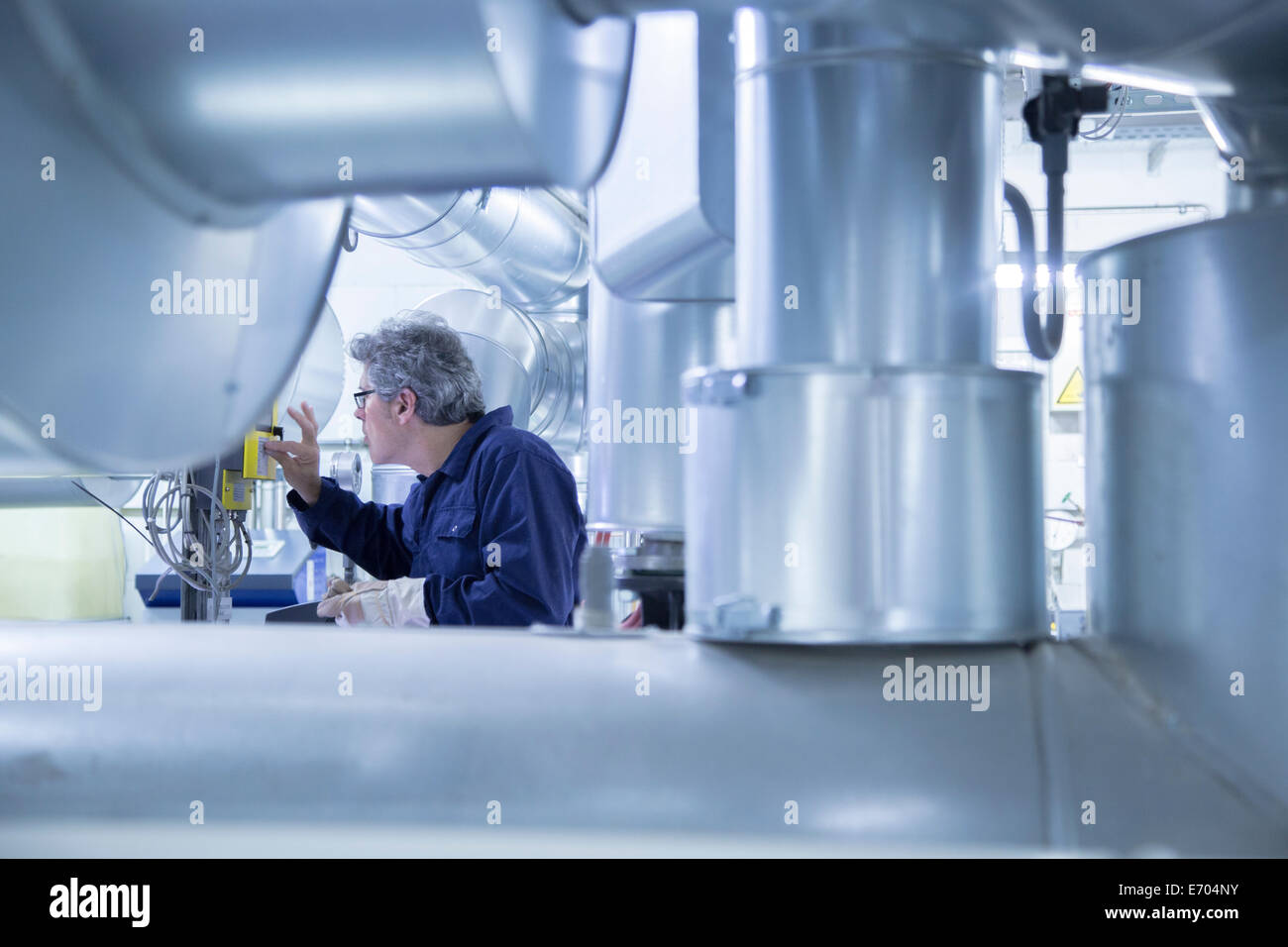 Engineer adjusting control panel in power station - Stock Image