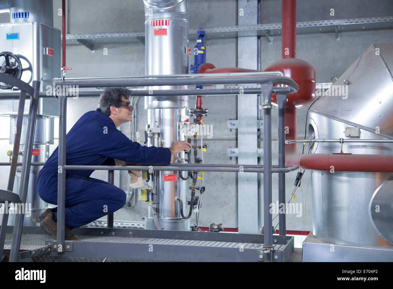 Engineer inspecting equipment from access platform in power station - Stock Image