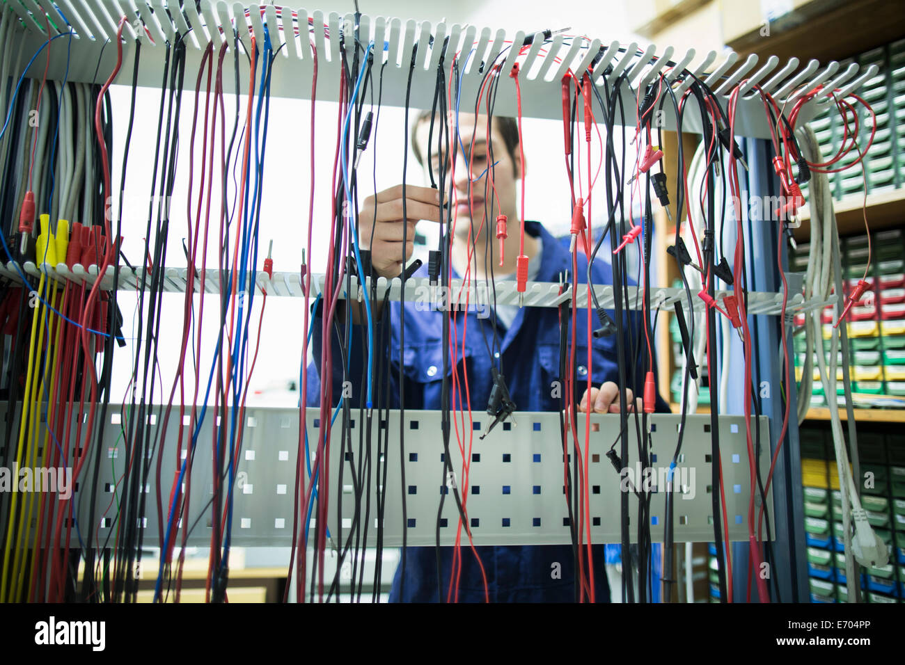 Male electrician selecting power cable in workshop - Stock Image