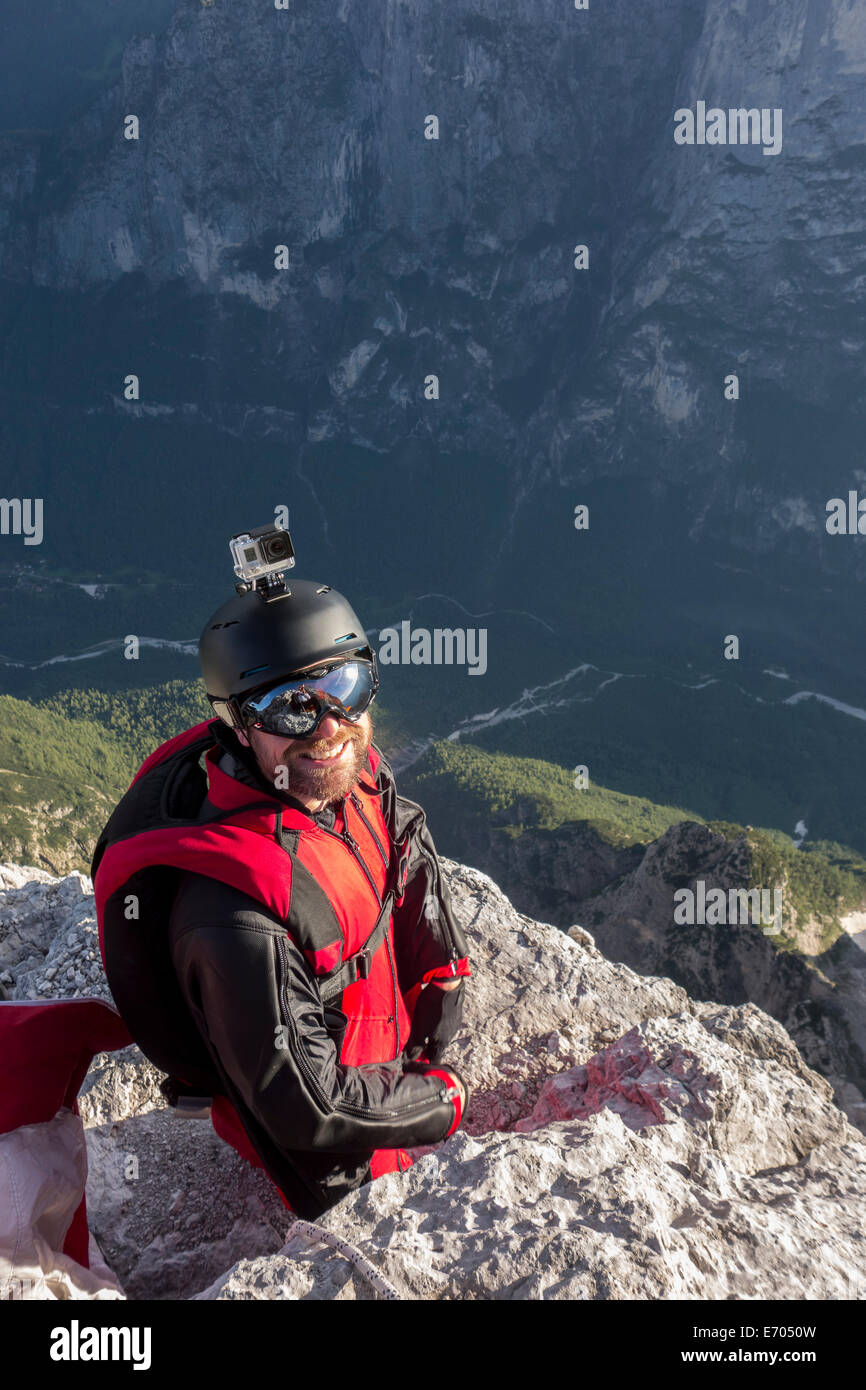 Portrait of BASE jumper on mountain edge, Alleghe, Dolomites, Italy - Stock Image