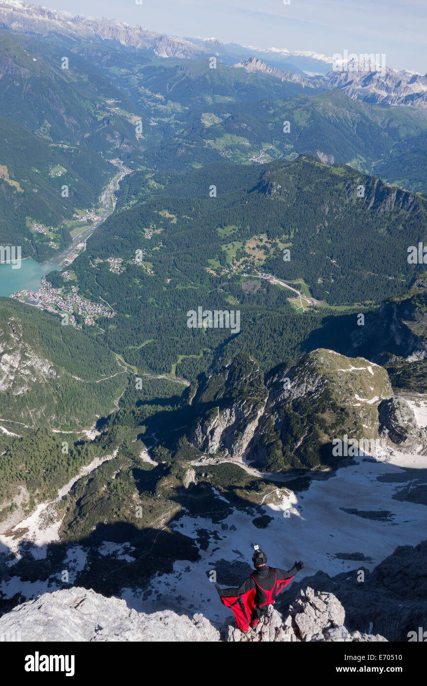 Male BASE jumper on mountain edge, Alleghe, Dolomites, Italy - Stock Image