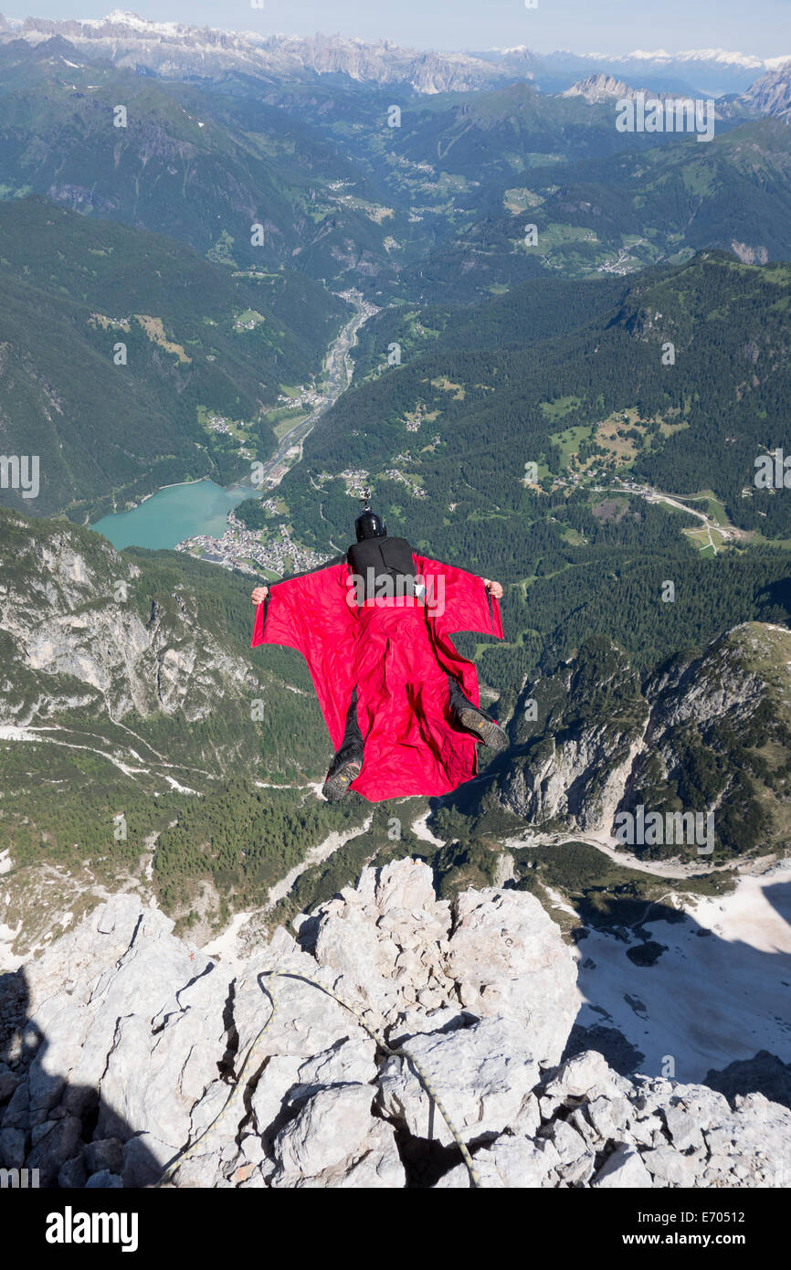 Mature man BASE jumping from mountain, Alleghe, Dolomites, Italy - Stock Image