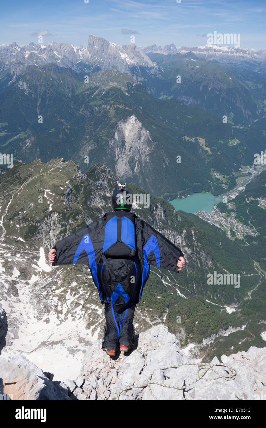 Mid adult man BASE jumping from mountain edge, Alleghe, Dolomites, Italy - Stock Image