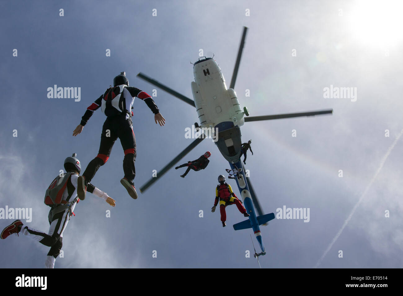Low angle view of helicopter and six skydivers free falling, Siofok, Somogy, Hungary Stock Photo