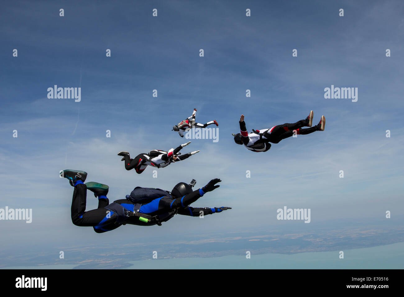 Four young adult male skydivers free falling, Siofok, Somogy, Hungary - Stock Image