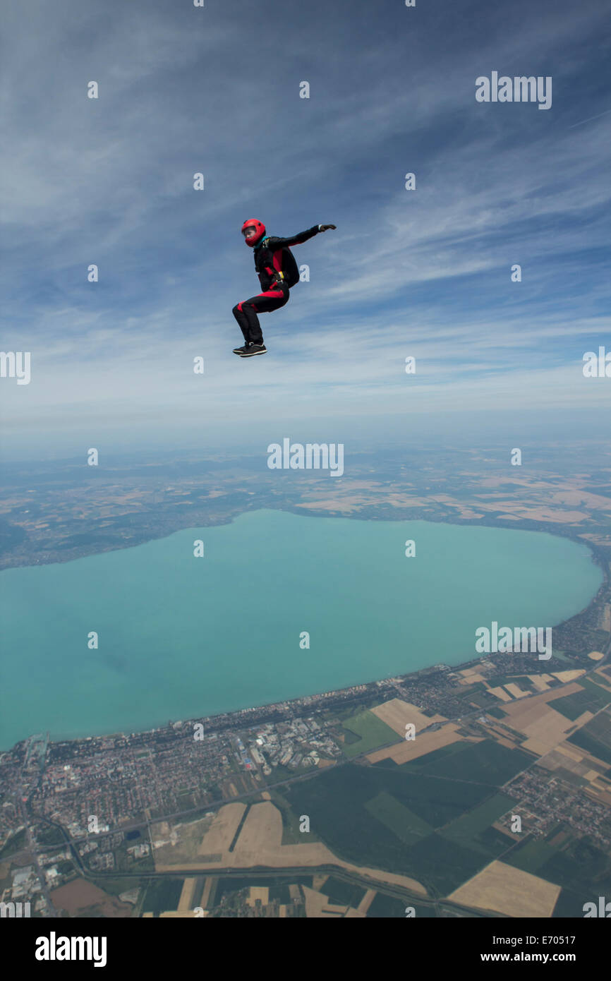 Female skydiver free falling above Siofok, Somogy, Hungary - Stock Image