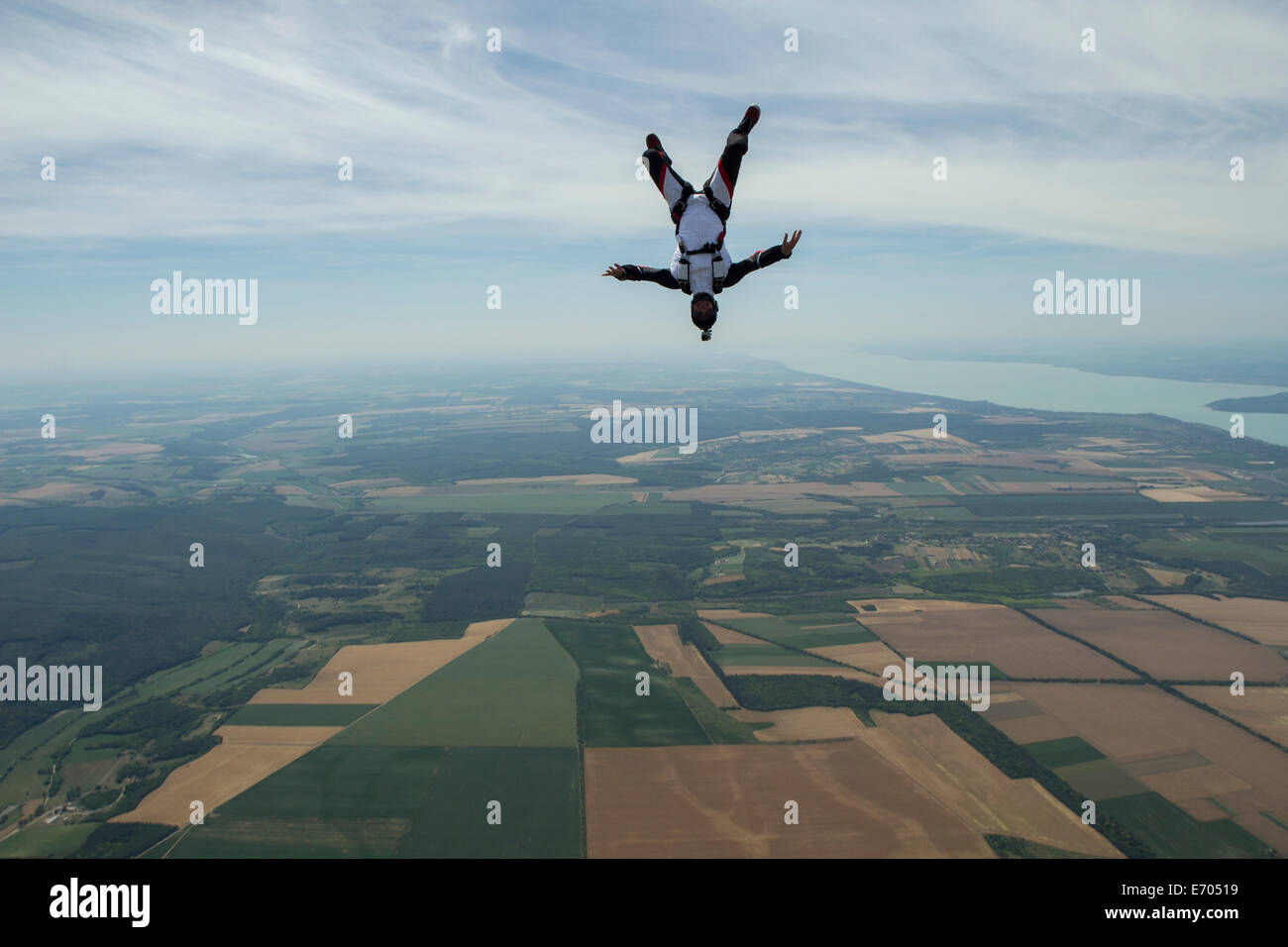 Male skydiver freeflying upside down above Siofok, Somogy, Hungary - Stock Image