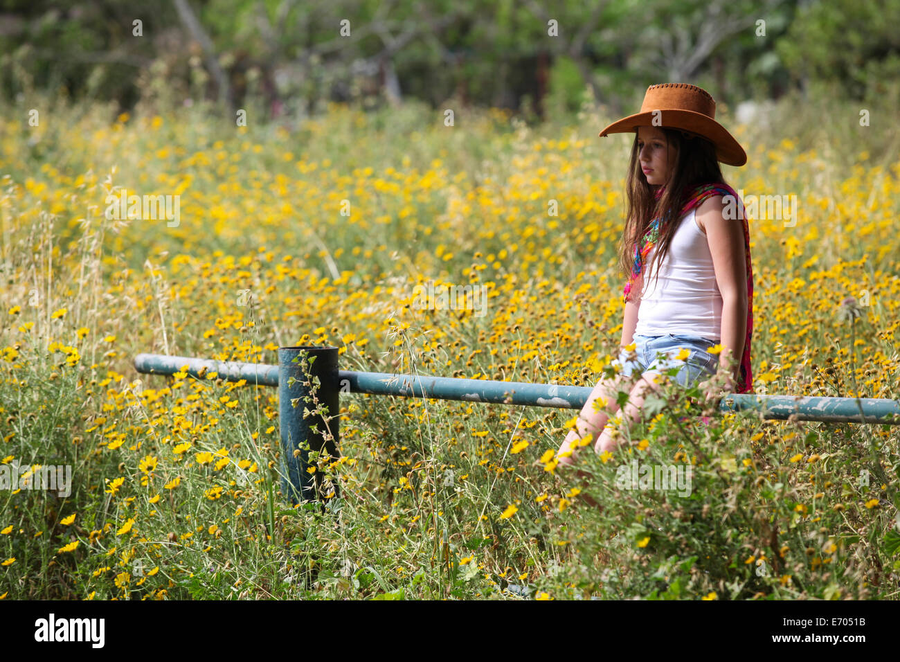 Sullen girl in cowboy hat sitting on fence in field - Stock Image