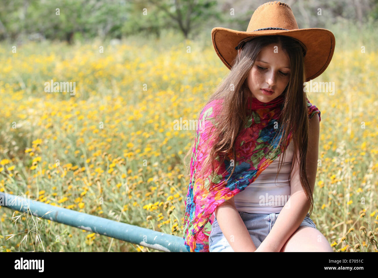 Sullen girl in cowboy hat sitting on fence gazing down - Stock Image