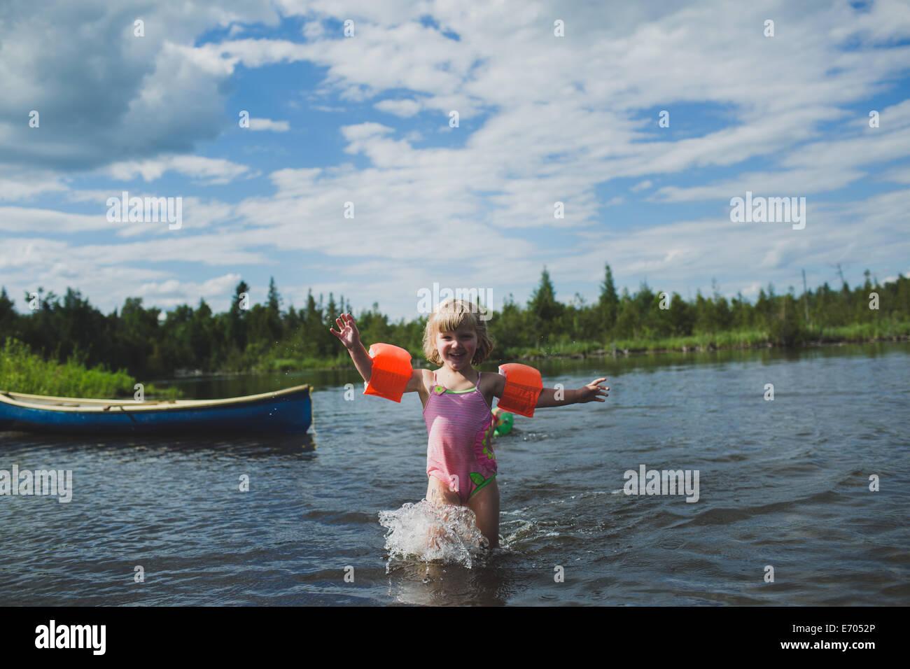 Three year old girl splashing in Indian river, Ontario, Canada - Stock Image
