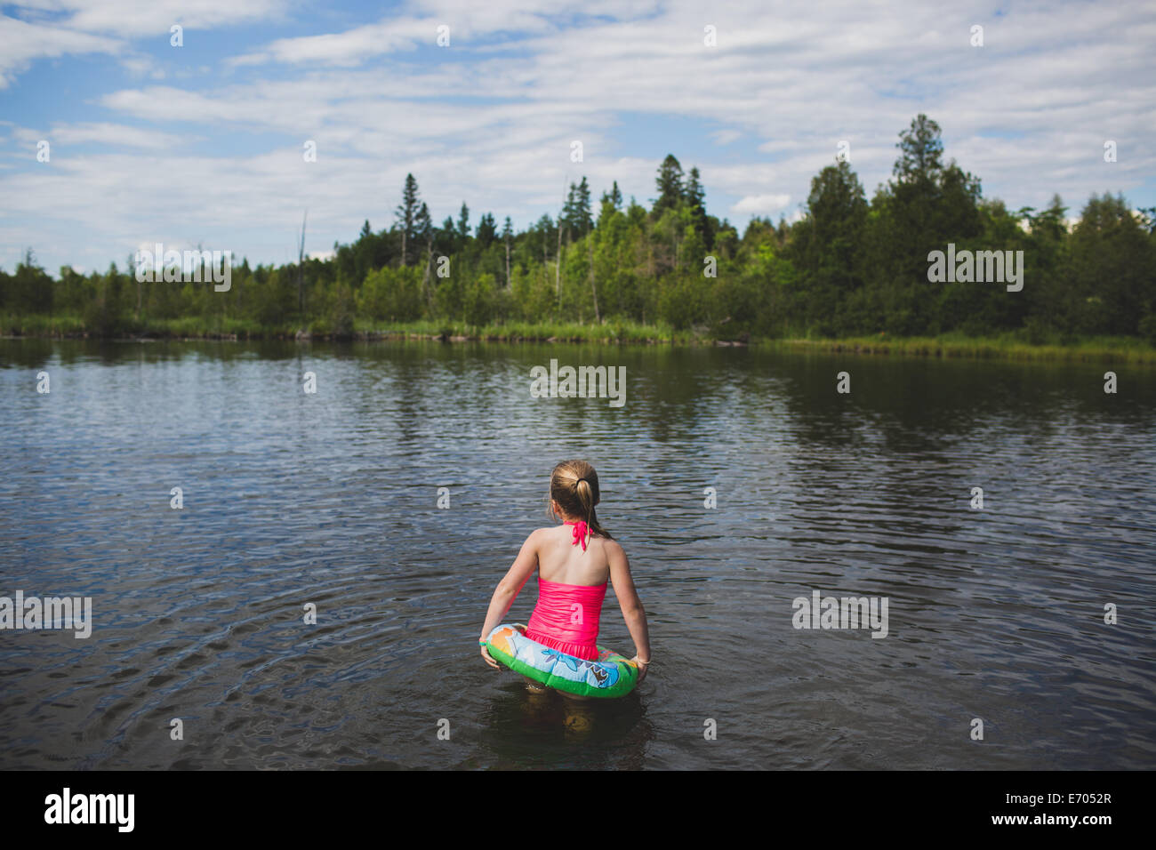 Rear view of girl with rubber ring in Indian river, Ontario, Canada - Stock Image