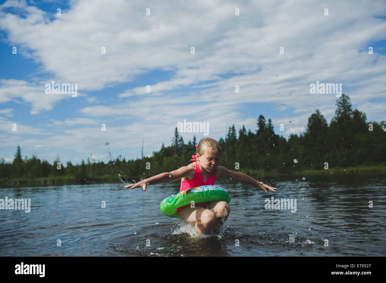 Girl with rubber ring jumping in Indian river, Ontario, Canada - Stock Image