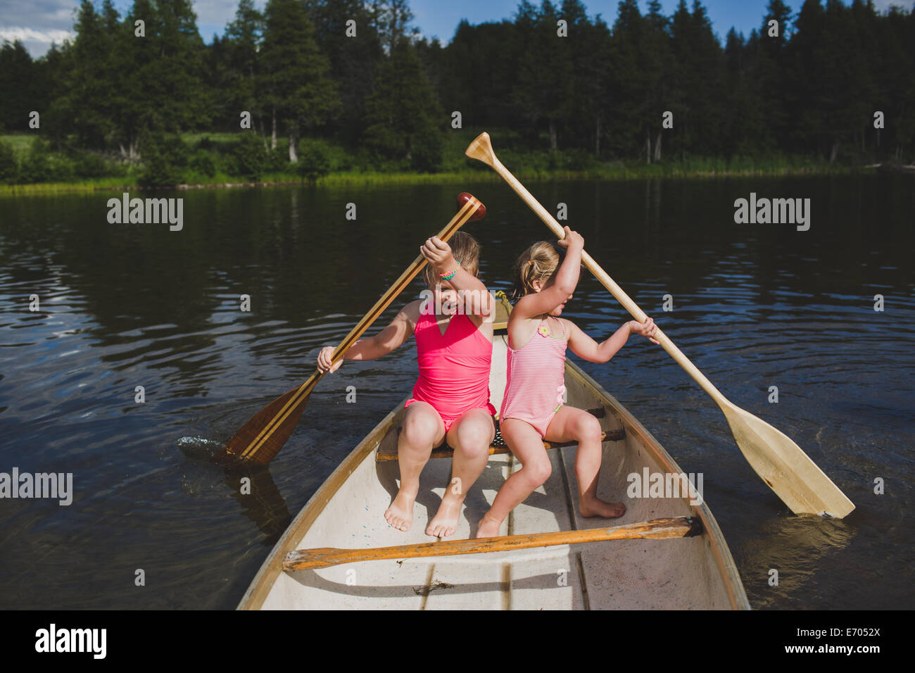 Two young sisters rowing in canoe on Indian river, Ontario, Canada Stock Photo