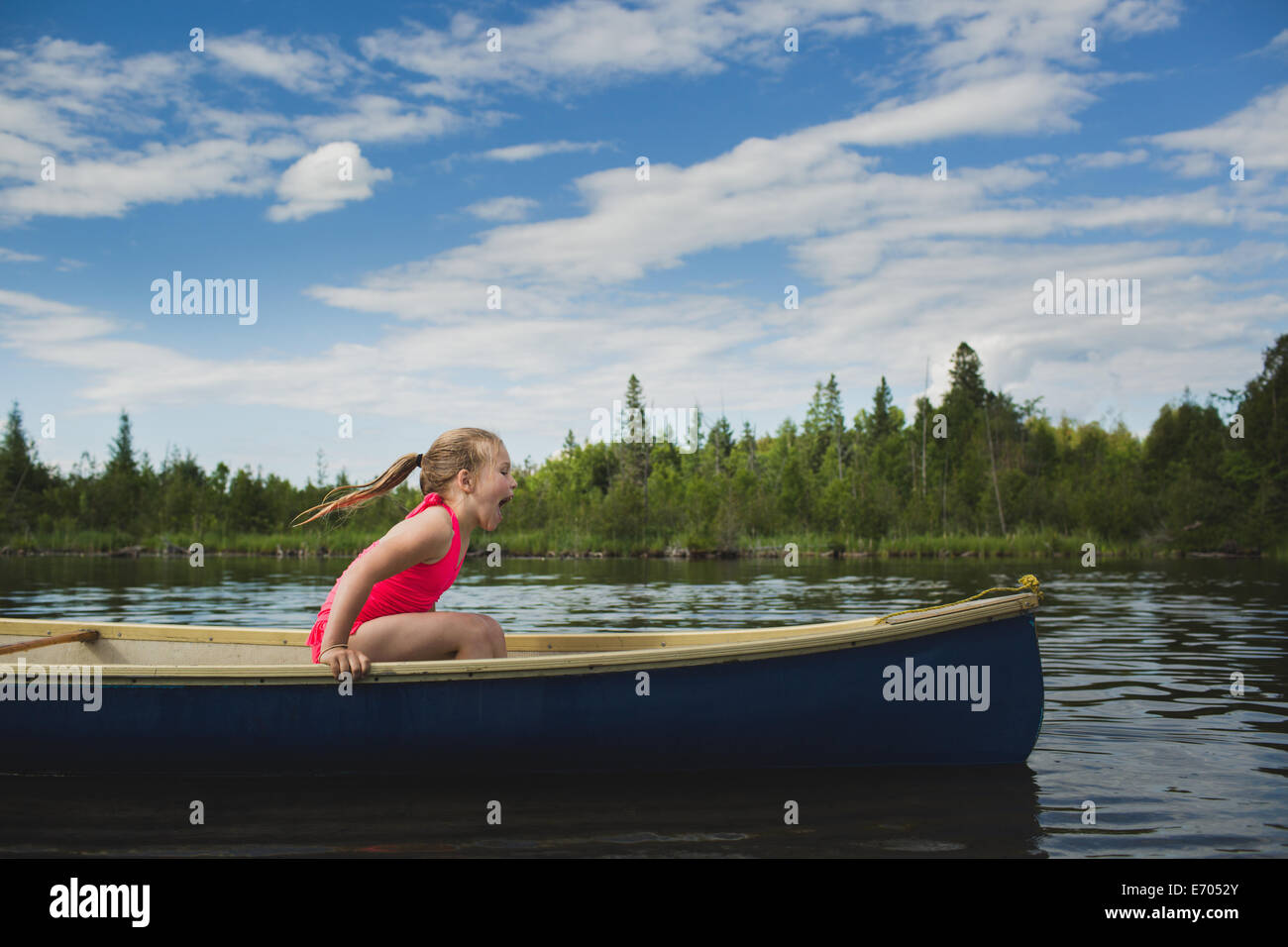 Excited girl sitting in canoe on Indian river, Ontario, Canada Stock Photo