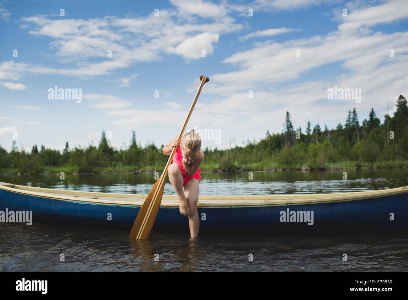 Curious girl looking down at water in Indian river, Ontario, Canada - Stock Image