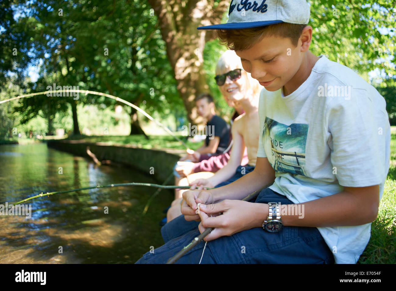 Boys holding sticks, fishing - Stock Image