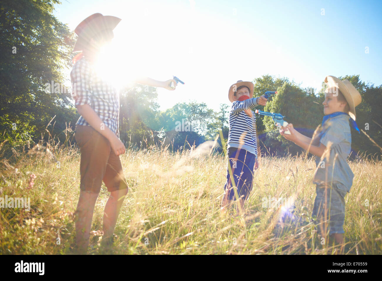 Three young boys dressed as cowboys, holding toy guns - Stock Image