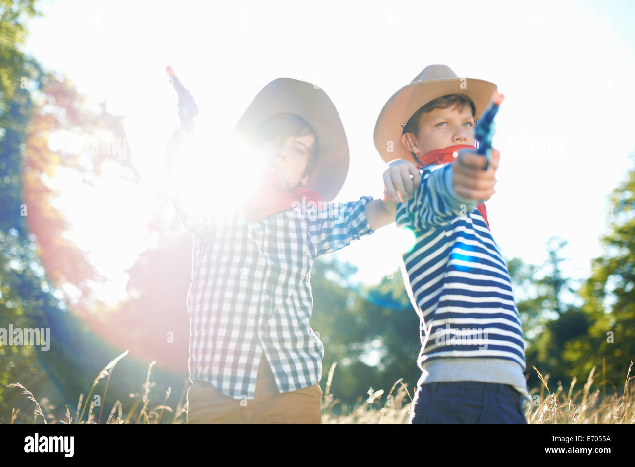 Two young boys dressed as cowboys, holding toy guns - Stock Image