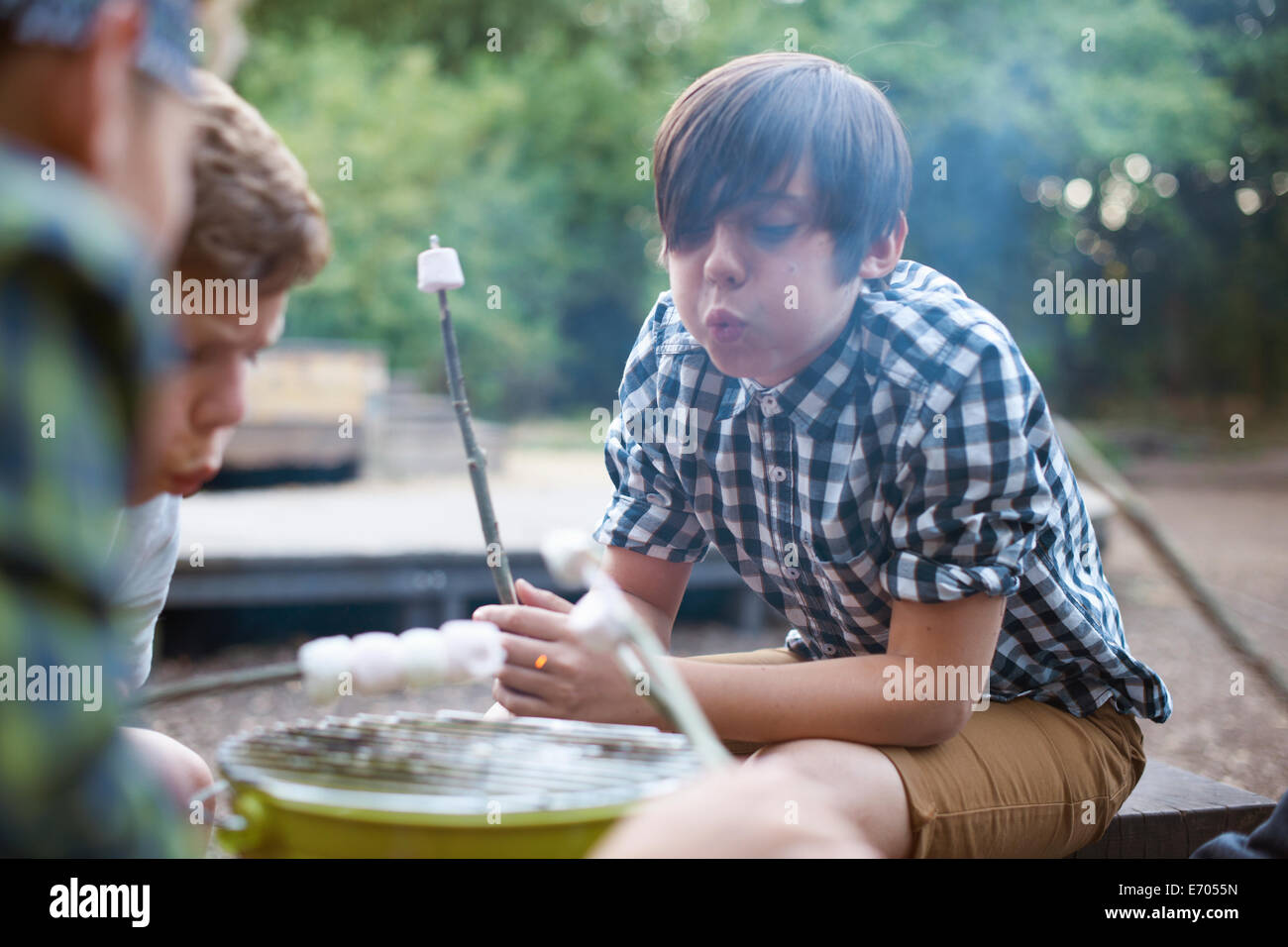 Group of young boys toasting marshmallows over bucket barbecue - Stock Image