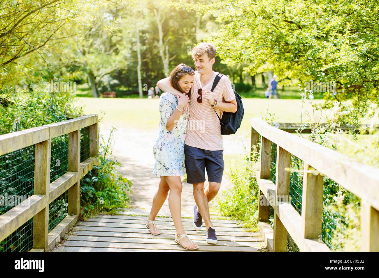 Couple walking over wooden bridge in the park - Stock Image