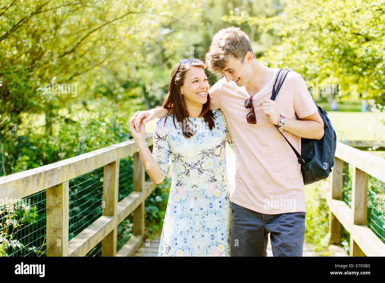 Couple walking over wooden bridge in the park Stock Photo