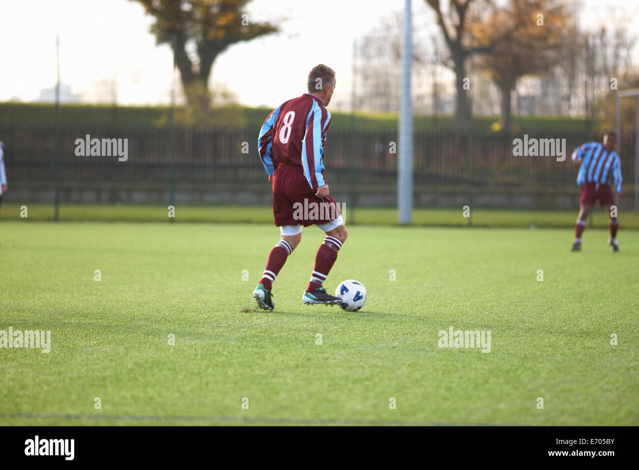 Football player with possession of ball - Stock Image