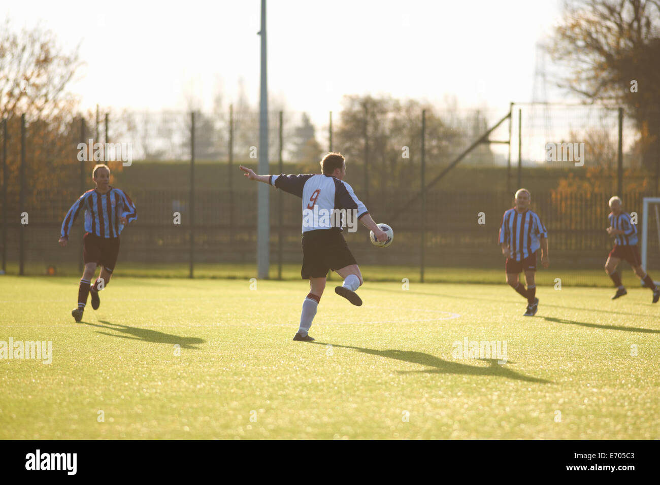 Football player kicking ball - Stock Image