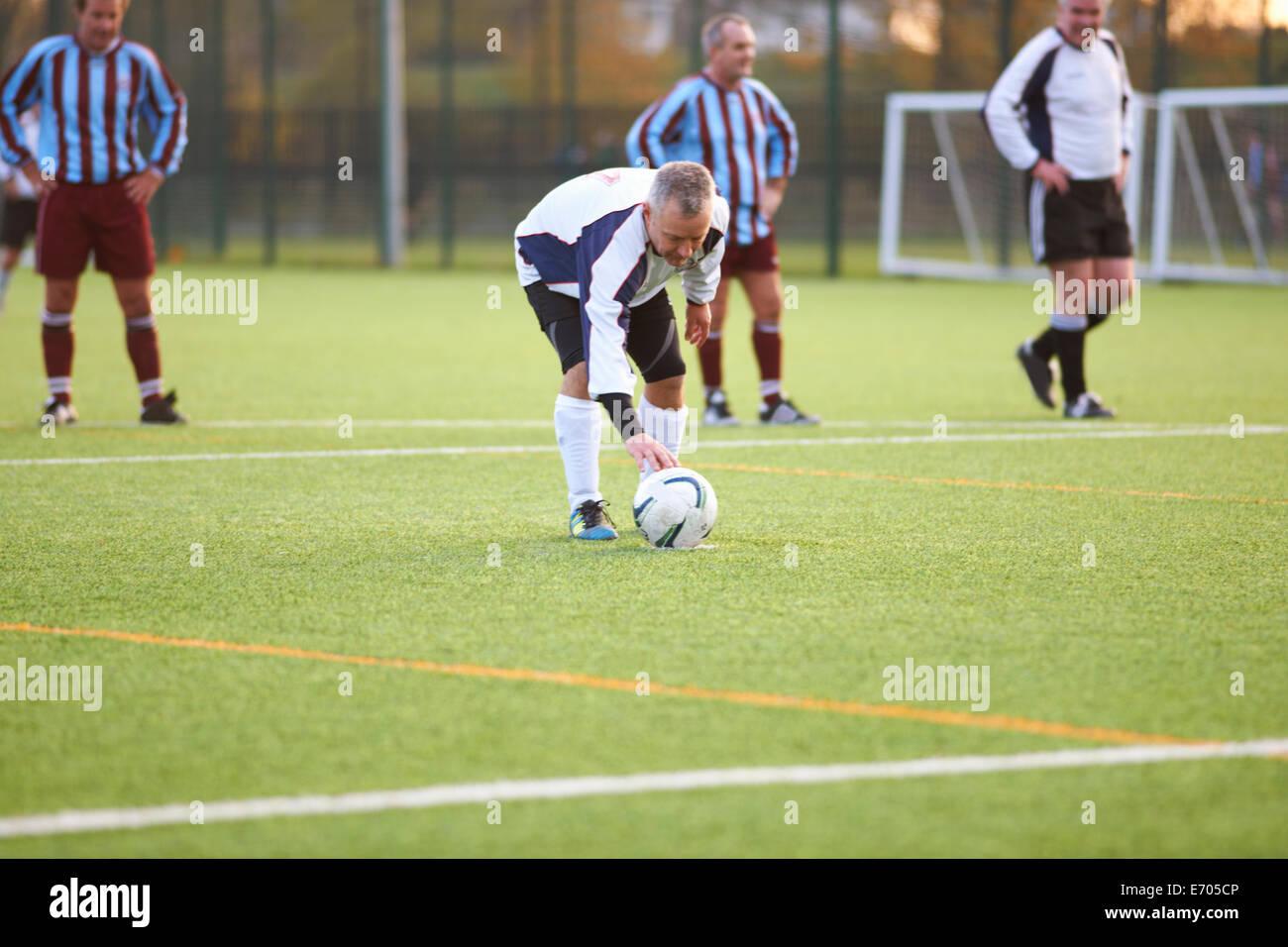 Football player positioning ball - Stock Image