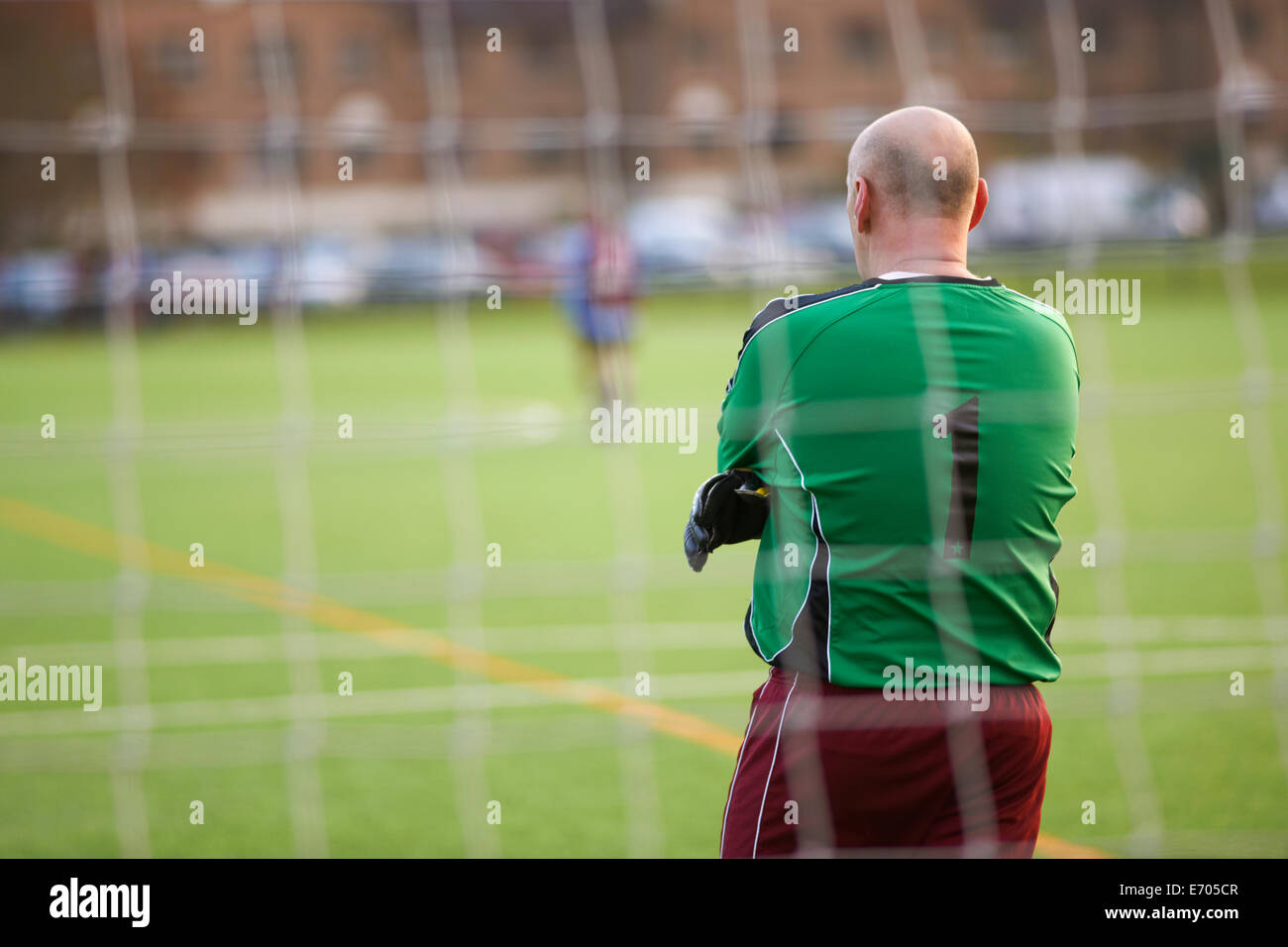 Rearview of goalie at football game Stock Photo