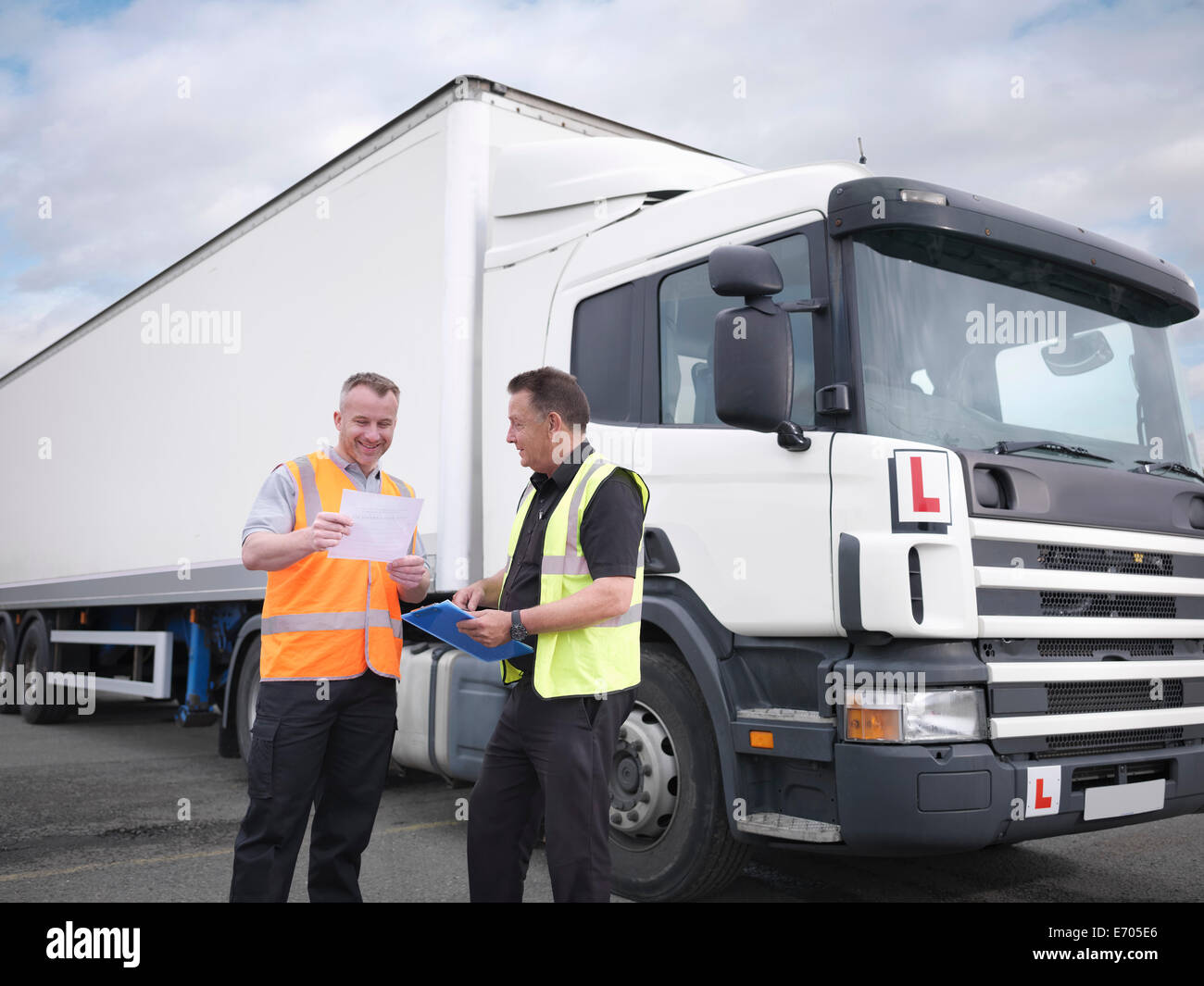 Trainee truck driver receiving pass certificate from instructor - Stock Image