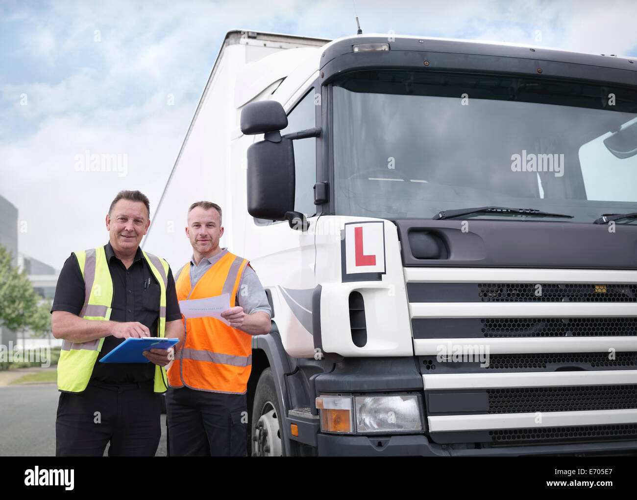 Portrait of trainee truck driver receiving pass certificate from instructor - Stock Image