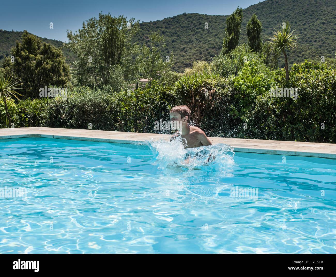 Boy splashing and playing in swimming pool, Capoterra, Sardinia, Italy Stock Photo