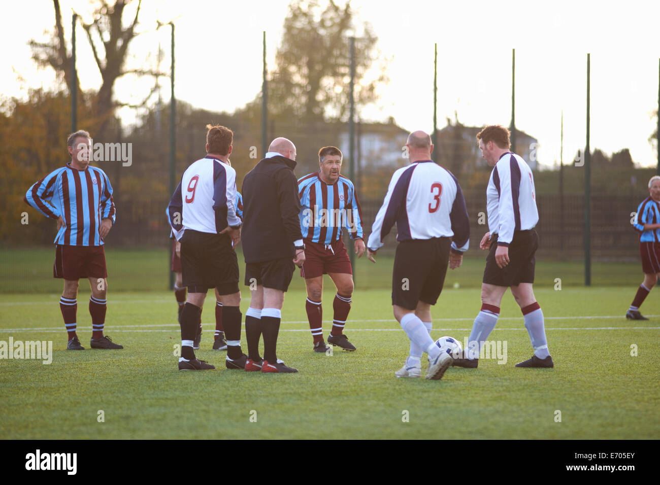Referee and football players settling dispute - Stock Image