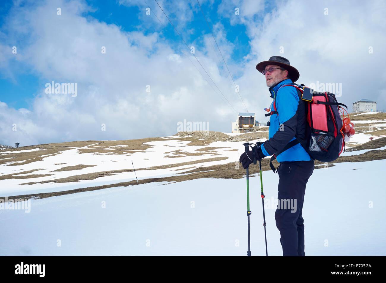 Mature man with hiking poles, Bucegi Mountains, Transylvania, Romania - Stock Image