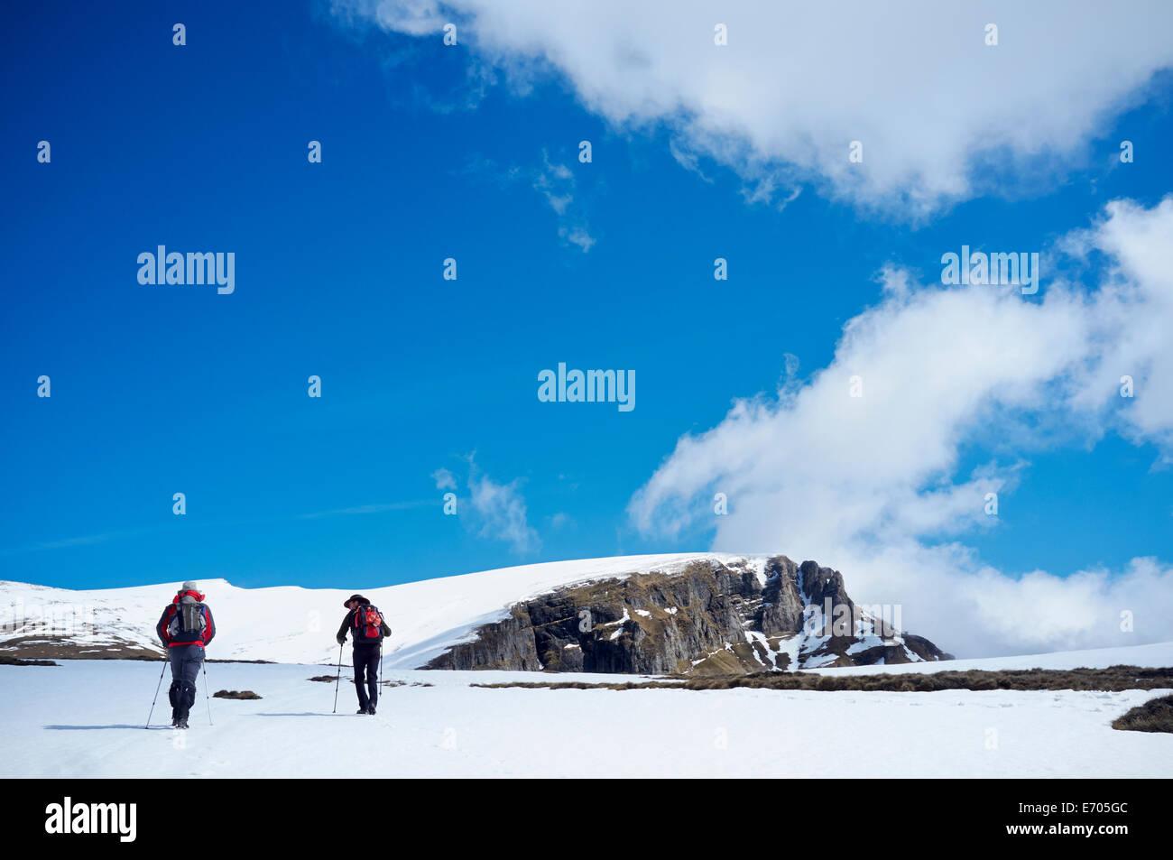 Two men hiking in snow, Bucegi Mountains, Transylvania, Romania - Stock Image